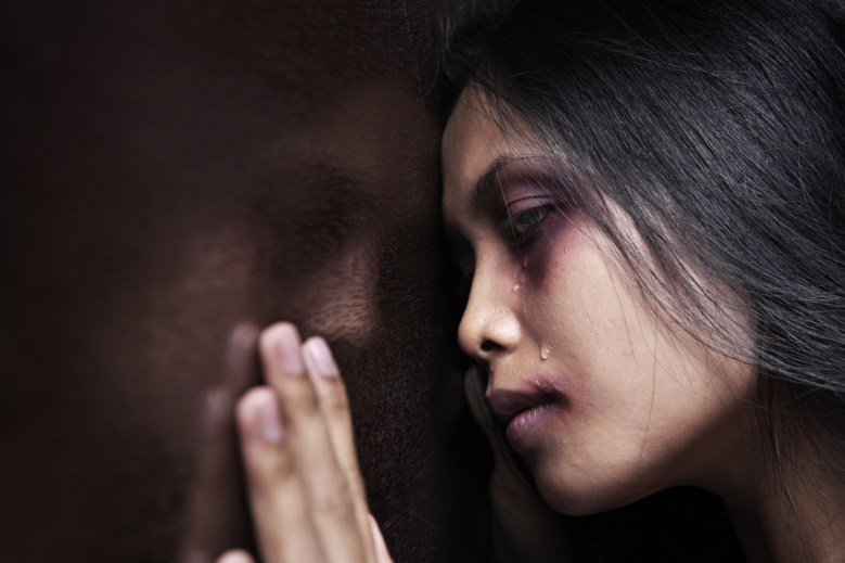 Injured woman leaning sadly on wooden wall, concept for domestic violence