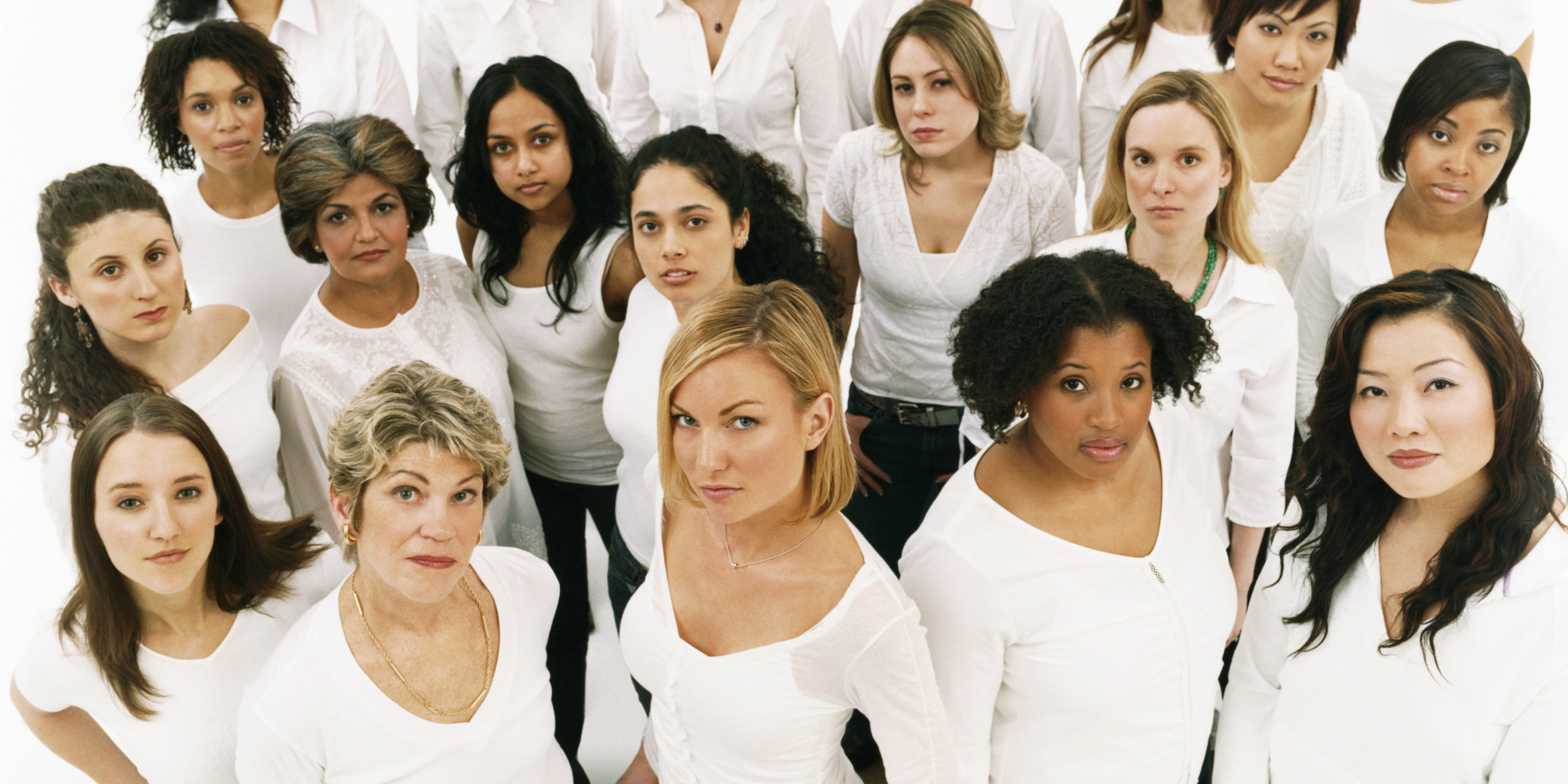 Studio Portrait of a Mixed Age, Multiethnic, Large Group of Displeased Women Wearing White Tops