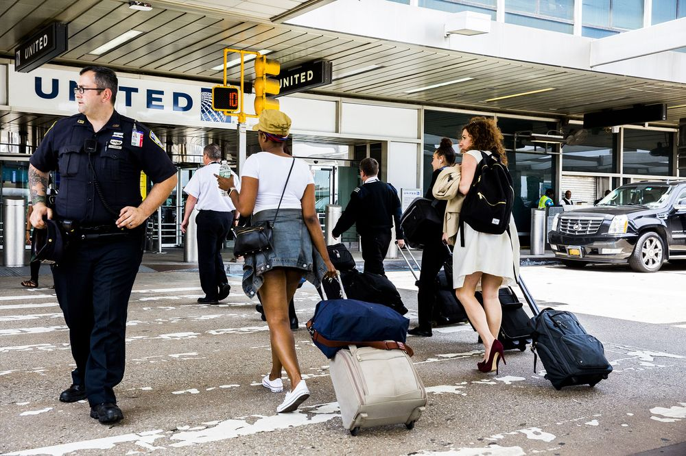 Travelers pull luggage while arriving at LaGuardia Airport (LGA) in New York, U.S., on June 29. Photographer: David Williams/Bloomberg