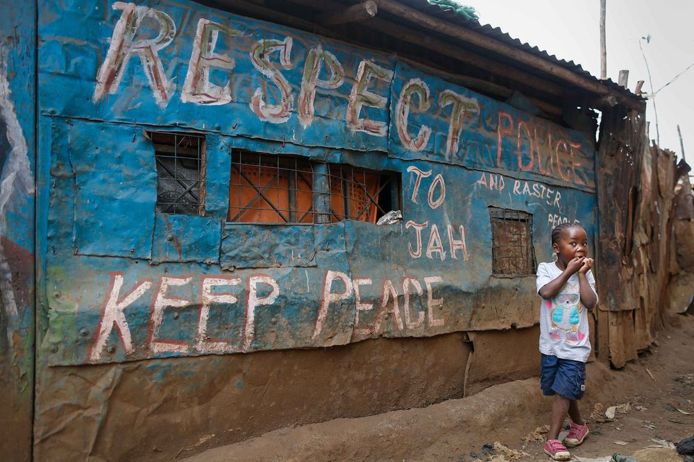 A young girl walks in front of a pub decorated with messages of peace painted during the 2007-08 general elections in Kenya—where post-election violence killed more than a thousand people—in Kibera slum, one of opposition leader Raila Odinga's strongholds in the capital Nairobi, in July 2017.   Photographer: DAI KUROKAWA/EPA/Redux