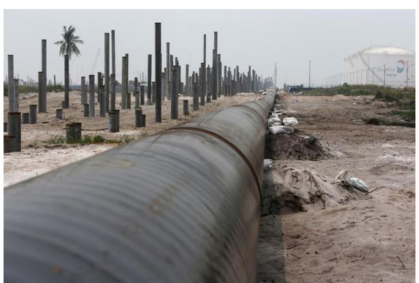 An oil pipeline is laid next to the Vopak-Dialog oil storage facility (R) and a Refinery and Petrochemical Integrated Development (RAPID) project construction site in Pangerang in Malaysia's southern state of Johor October 6, 2015. Edgar Su/File Photo