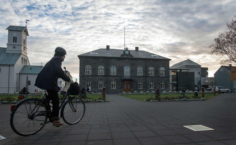 A woman cycles past the Althingi Parliament building in Reykjavik.  Photographer: Halldor Kolbeins/AFP via Getty Images