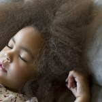 Mixed race girl sleeping on sofa