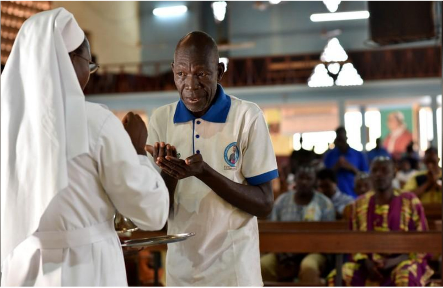 A catholic man receives communion at the cathedral of Our Lady of Kaya in the city of Kaya, Burkina Faso May 16, 2019. REUTERS/Anne Mimault