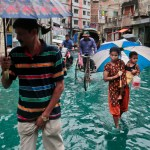 Bangladeshi people walk through a waterlogged street after heavy rainfall in Dhaka, Bangladesh, on Saturday, May 21, 2016. A cyclone unleashed heavy rain and strong winds on Bangladesh's southern coastal region on Saturday, killing at least 11 people and forcing hundreds of thousands from their homes. Mixing of rain water and toxic waste from industries has turned water into green. Photo: AP