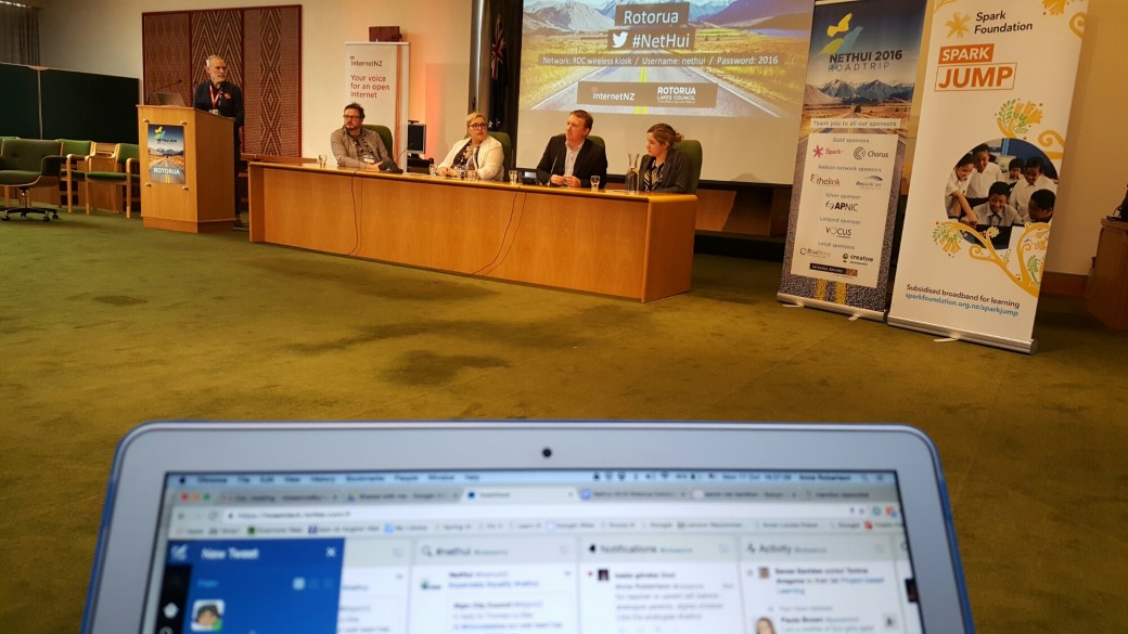 in the foreground the screen of a laptop. The viewer is looking over it at a panel of people sitting behind a wooden desk. There is a speaker at a lectern to the left of them