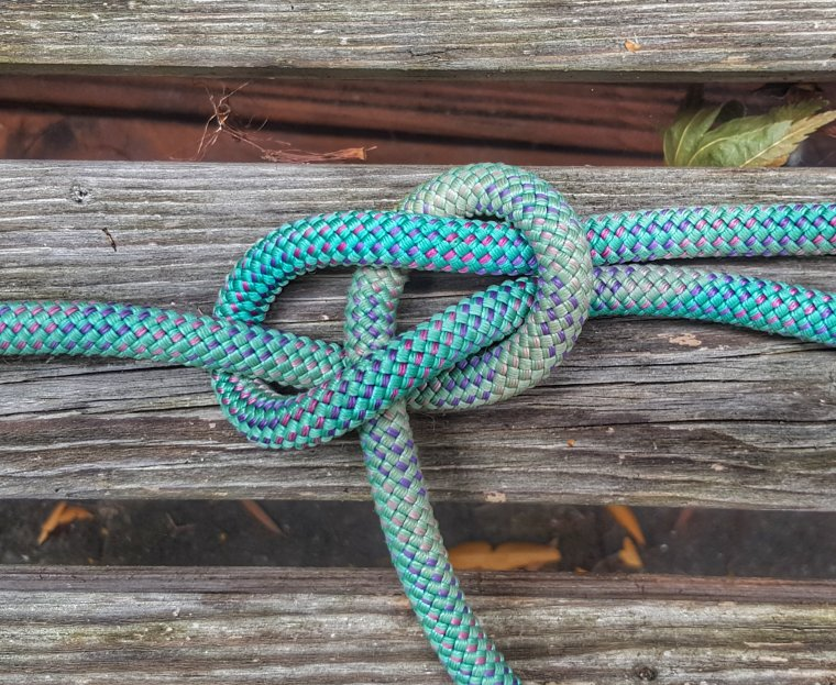 bowline knot in blue caving rope speckled with pink on a wooden bench