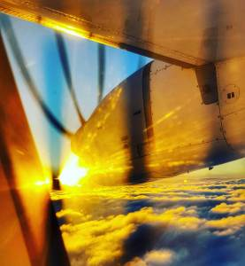 Nose cone of a plane heading into the rising sun. Propeller motion frozen in black stripes against the blue sky. Clouds below.