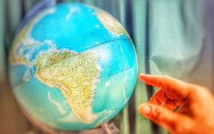 a globe showing Africa and a hand pointing to the Pacific