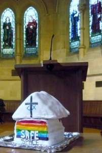 A rainbow cake decorated with the words 'Safe Space' and the United Reformed Church logo