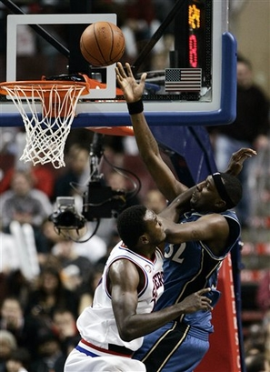 Andray Blatche of the Wizards  is fouled by  Samuel Dalembert of  the  76 ers'.......