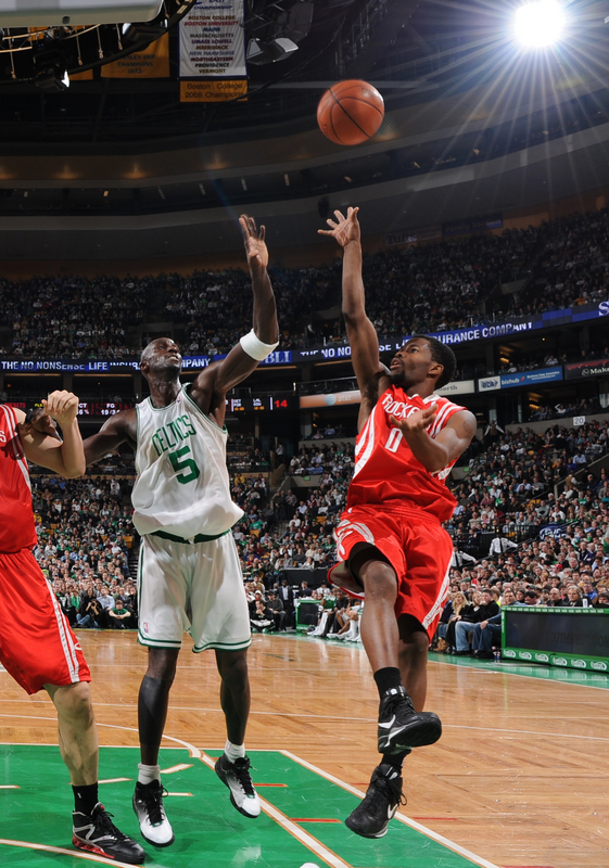 Garnett  tries  to  defend the  shot of the Rockets Aaron  Brooks .......