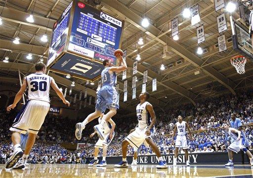 Duke's  John Scheyer (30)  watches  as  North Carolina's  Tyler  Hansbrough shoots  the jumper over  Lance Thomas  of the Blue Devils
