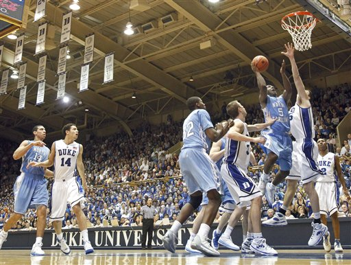 Ty Lawson of  North Carolina  drives  for  the  basket  as  Duke's  Brian Zoubek tries  to defend  the  play .  ...................