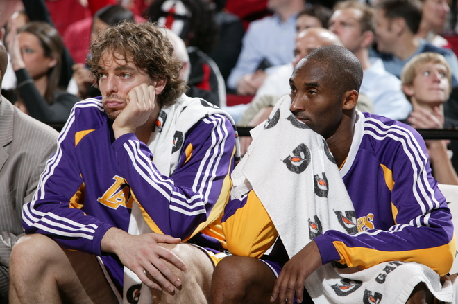 A subdued  Kobe Bryant (right) and  teammate Pau Gasol seated on  the bench  look  on  in  the  waning  moments of  the  game.  The  Lakers  would  go on  to  lose the  game  decisively  against  their  Western Conference rivals the Portland Trailblazers 111-94.   picture appears courtesy of   nbae/getty  images/ Sam Forencich .........