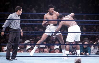 Ali   connects  to  the  head  of  Frazier  and  has  him  somewhat  dazed .     The   fighters  would  end  having  a  trilogy   of  bouts   which've  become  synonymous  with   both  of  their  careers.