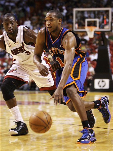 Chris Duhon  of  the  New York Knicks  tries to evade the  defensive play  of  the  Heat's  Dwyane  Wade  picture  appears  courtesy of  ap/photo/Lyne  Sladky ...............