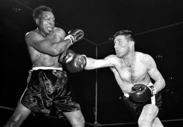 Moore  (left)  faces  a  challenge  from  France's  Yvon  Durrelle  for  his   lightheavyweight  title  .  Moore   would  go  on  to  defeat the  Frenchman .