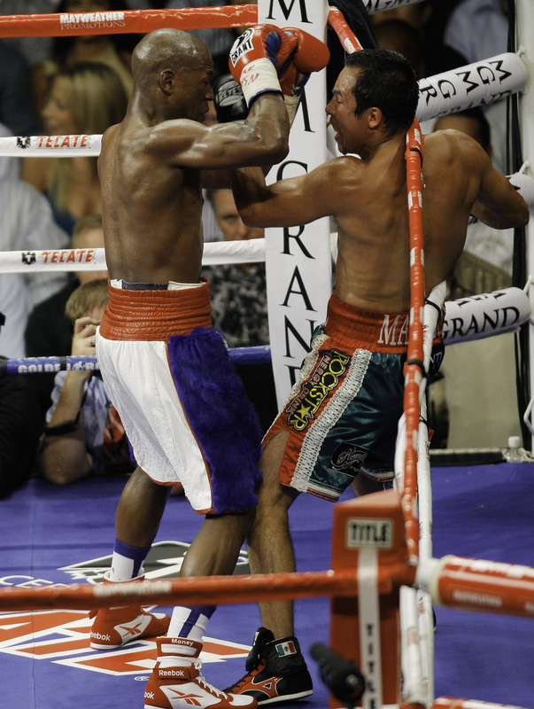 Mayweather  and   Marquez  exchange   punches   while  on  the  ropes .    picture  appears   courtesy of  getty images/  Eric  Jamison................