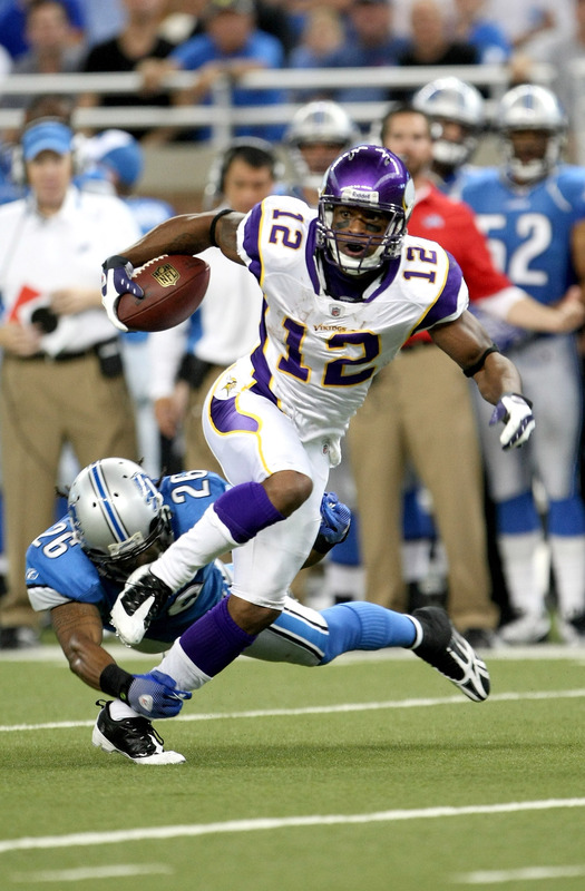 Vikings'  wide  receiver Percy Harvin   (12) evades  Lions'  safety   Louis  Delmas   in  an  NFL game  at Ford  Field  ,  Detroit , Michigan.   picture appears courtesy  of getty  images/  Stephen  Dunn   ...............