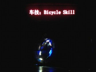 7 motorcycles ride around in a sphere in the dark.