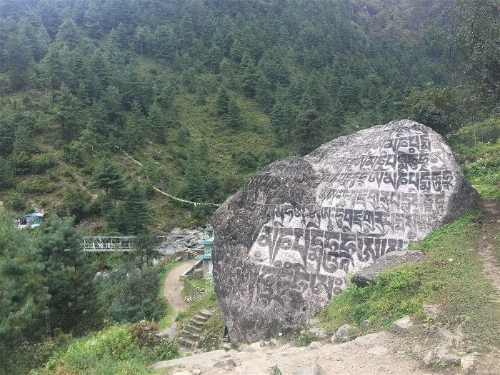 Humongous rocks throughout the trail stand as a religious scripts between hamlets on the road from Lukla to Phakding