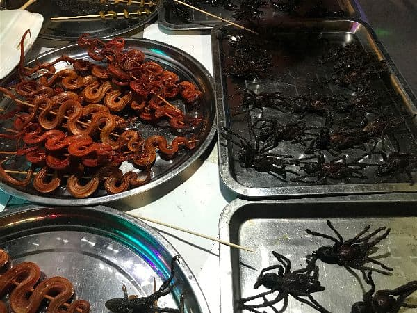 Tarantula - A not so delicious option to taste in Thailand and Cambodia. Notice the optional snake hanging out on that tray too?