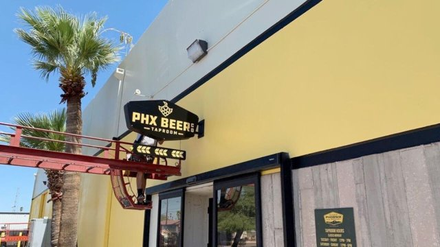 A worker installs new signage for the PHX Beer Co. Taproom.