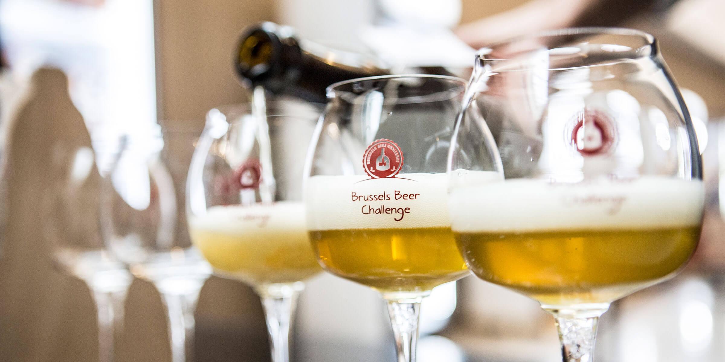 Beer being poured into Brussels Beer Challenge branded Teku glasses
