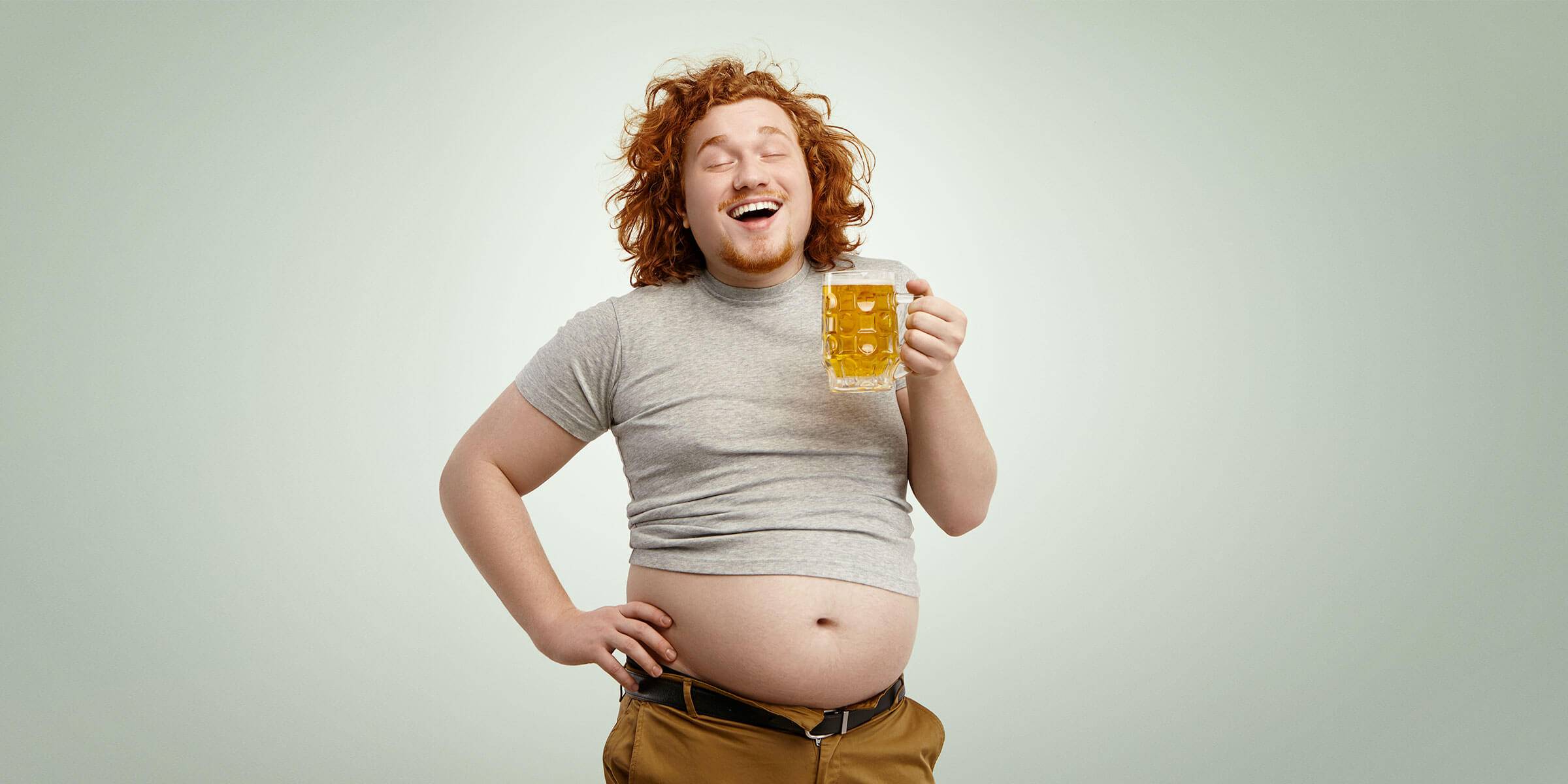 A fat red-haired man with an exposed beer belly is smiling while holding a mug of beer.