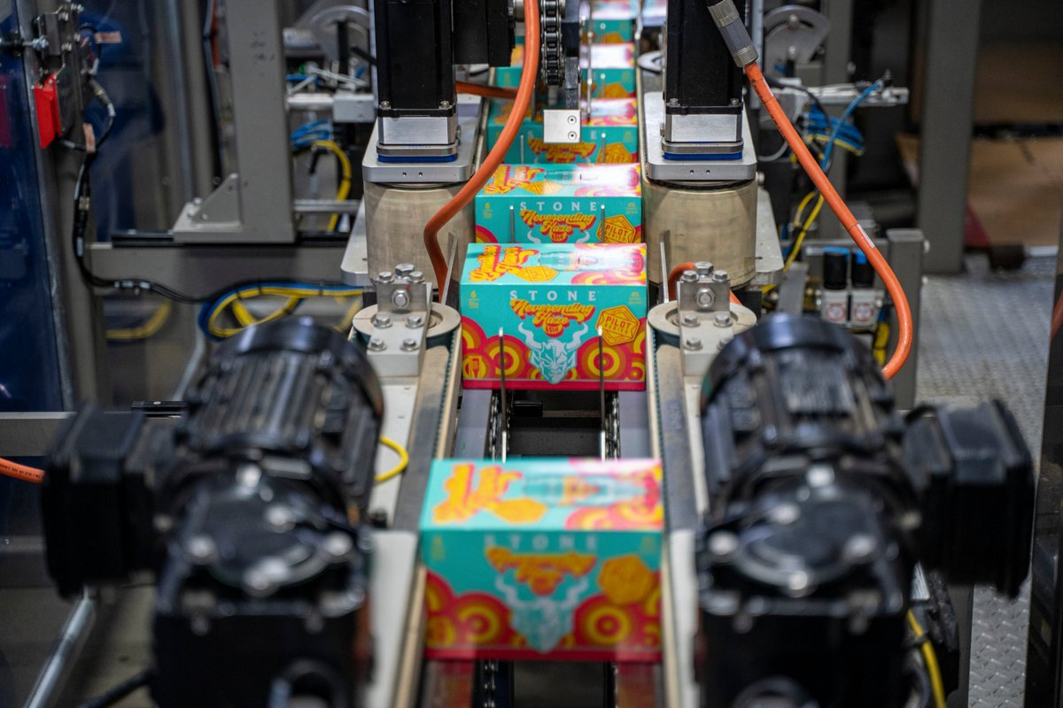 Packaging line of six packs of Neverending Haze by Stone Brewing