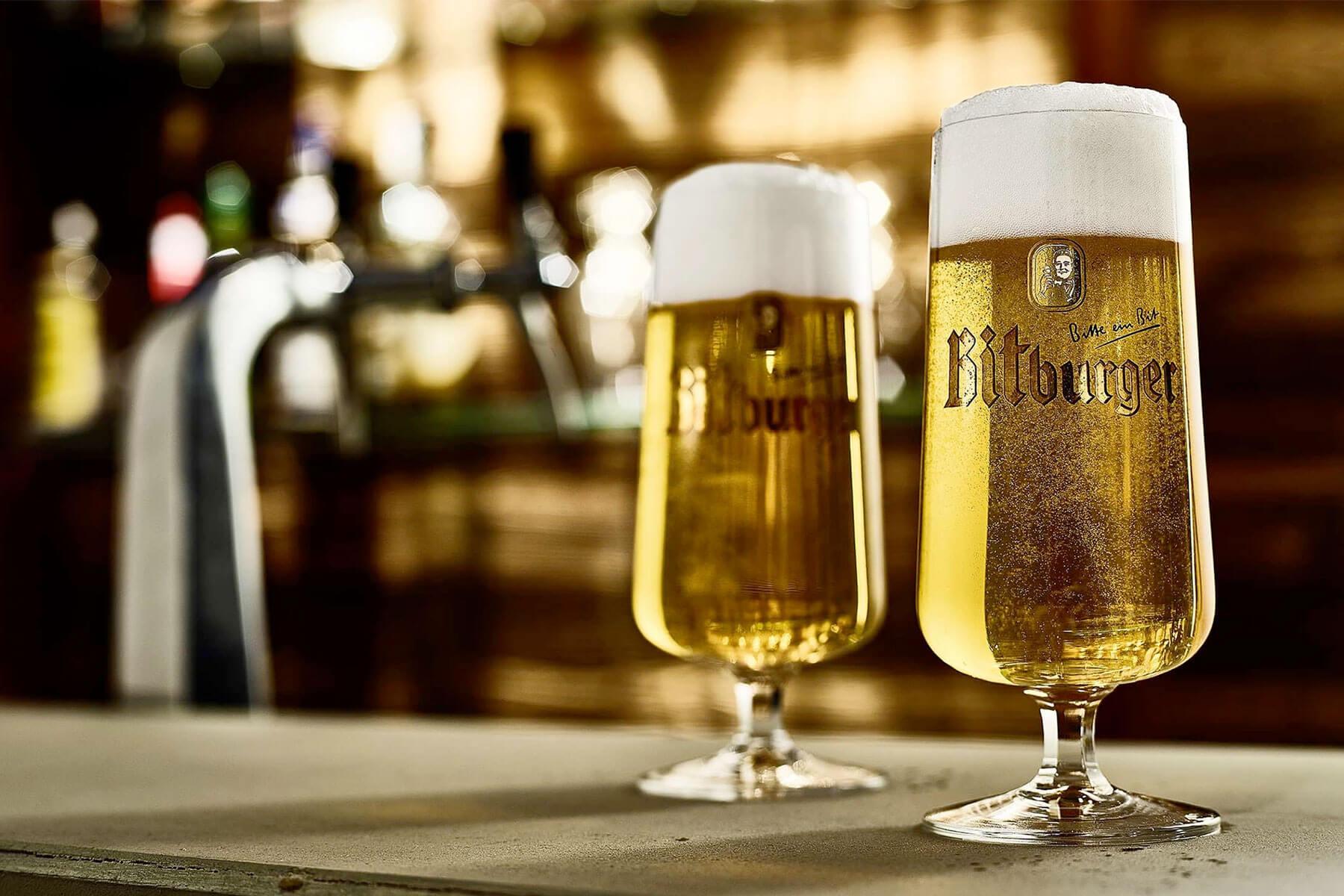 A pair of beers in Bitburger branded pilsner glasses