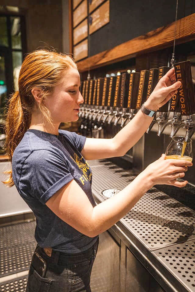 Female bartender pours a beer from inside the taproom at Fieldwork Brewing Company in Corte Madera, California