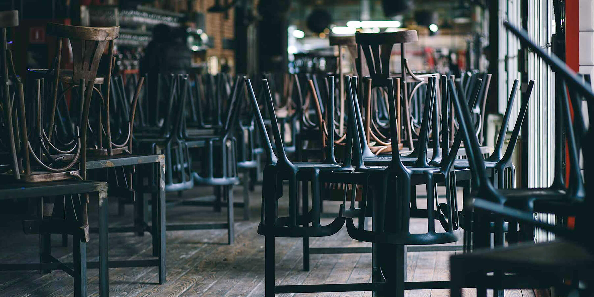 Chairs set atop tables in a closed bar