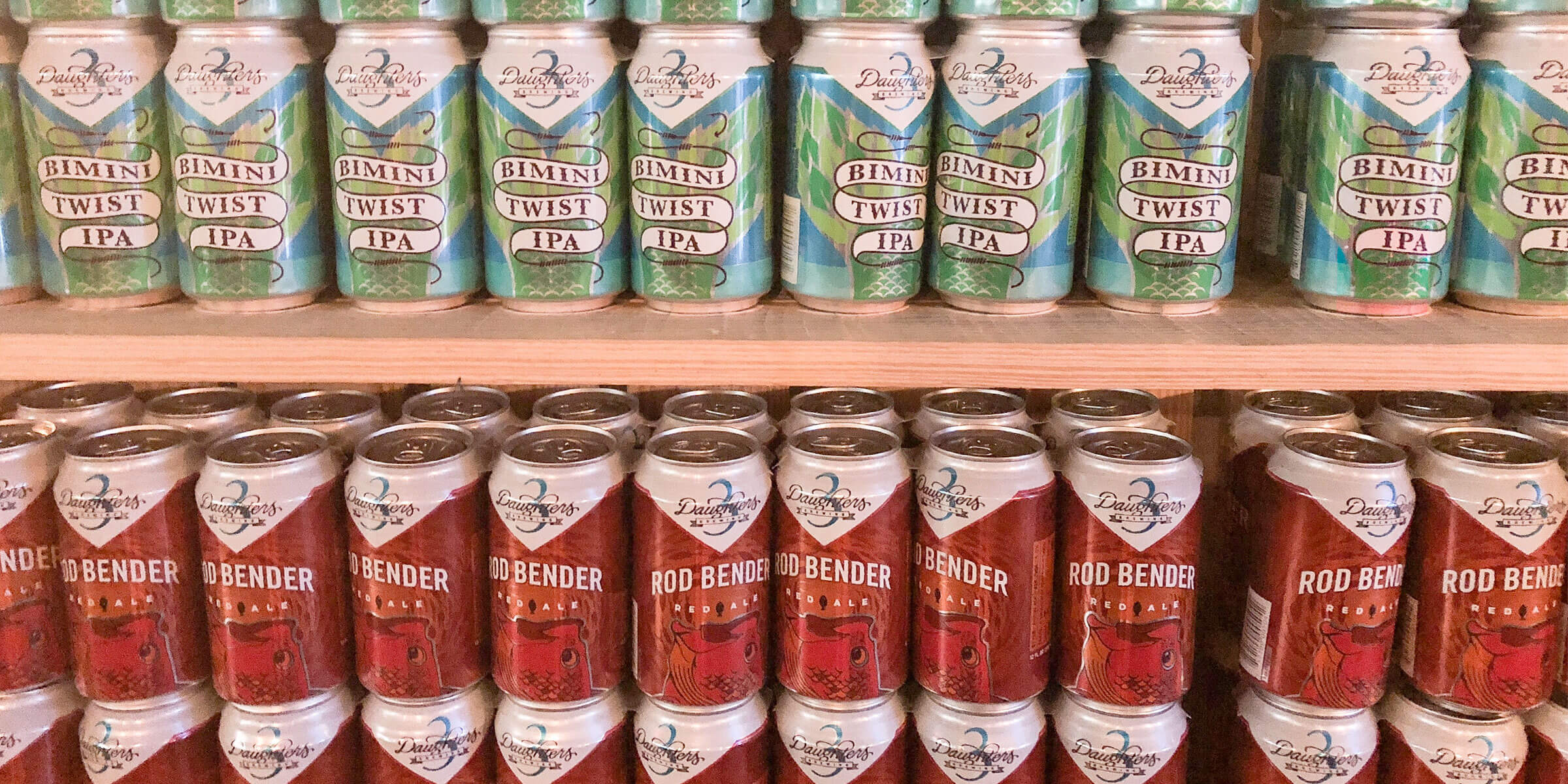 Rows of canned beers offered by 3 Daughters Brewing