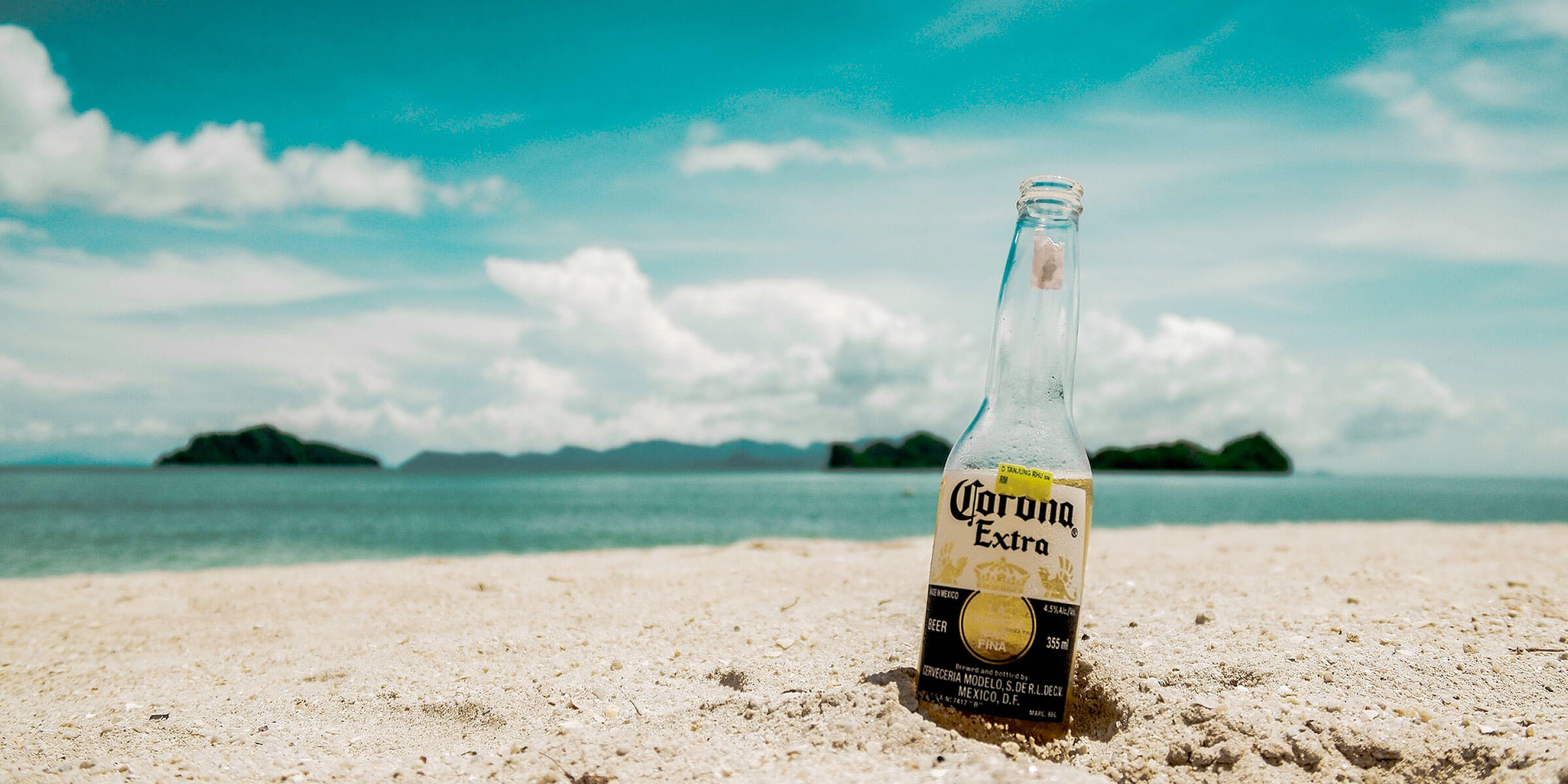An empty bottle of Corona Extra burrowed into the sand on a beach.