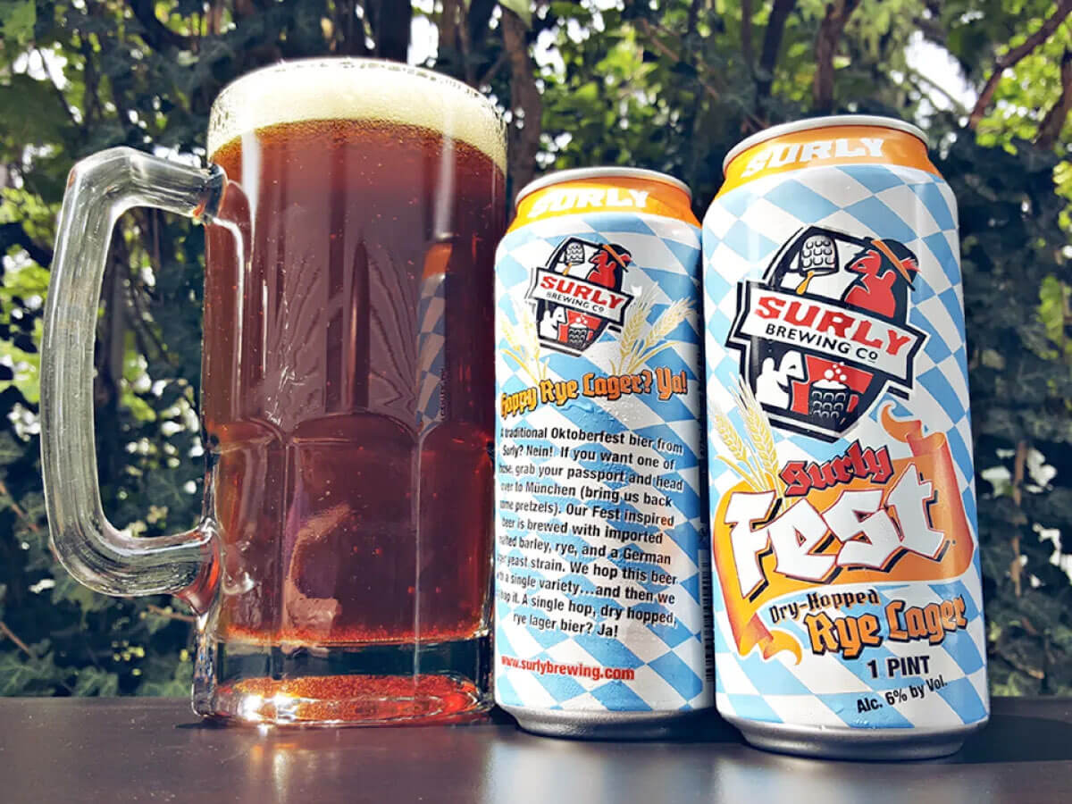 A pair of 16 oz. cans and beer mug of the Surly Fest Dry-Hopped Rye Lager by Surly Brewing Co.