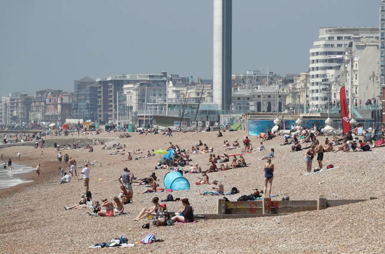 Beachgoers sits out in the sunshine along the coast of Brighton, England, as lockdown restrictions are eased