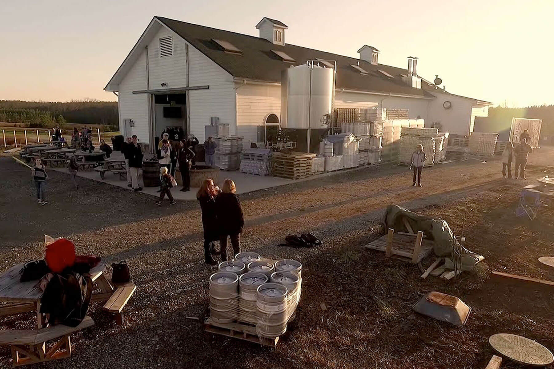 Guests enjoy beers outside Lickinghole Creek Craft Brewery at sunset in Goochland, Virginia