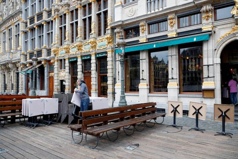 An employee prepares the terraces of a bar in central Brussels, as the country began easing lockdown restrictions following the coronavirus disease (COVID-19) outbreak in Belgium (REUTERS/Francois Lenoir)