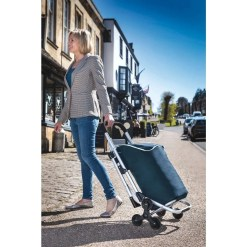 Bergman® 3-in-1 Shopping Trolley With Integrated Seat. Bergman being pulled along a street by a woman