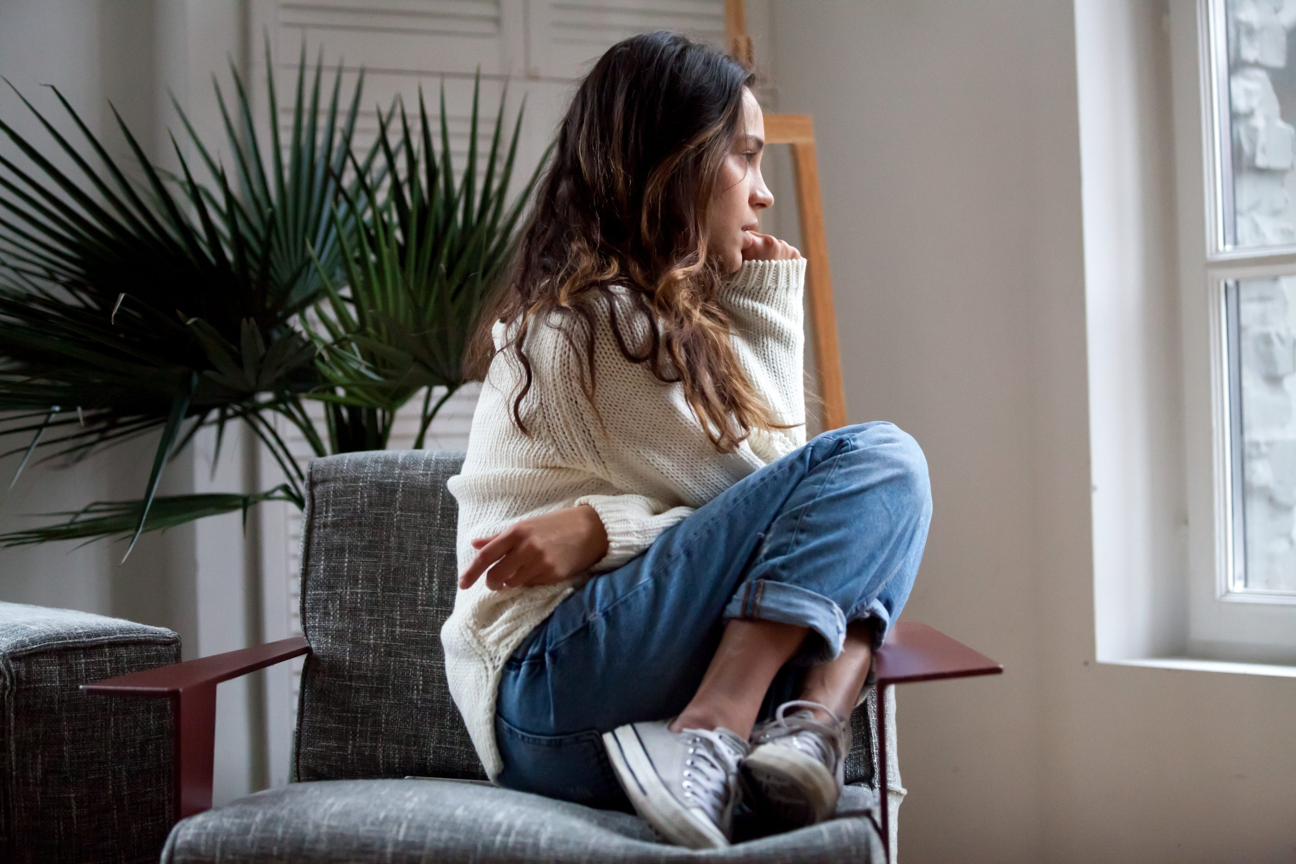 Sad thoughtful girl sitting on chair feeling anxiety depressed or lonely absolutely adell