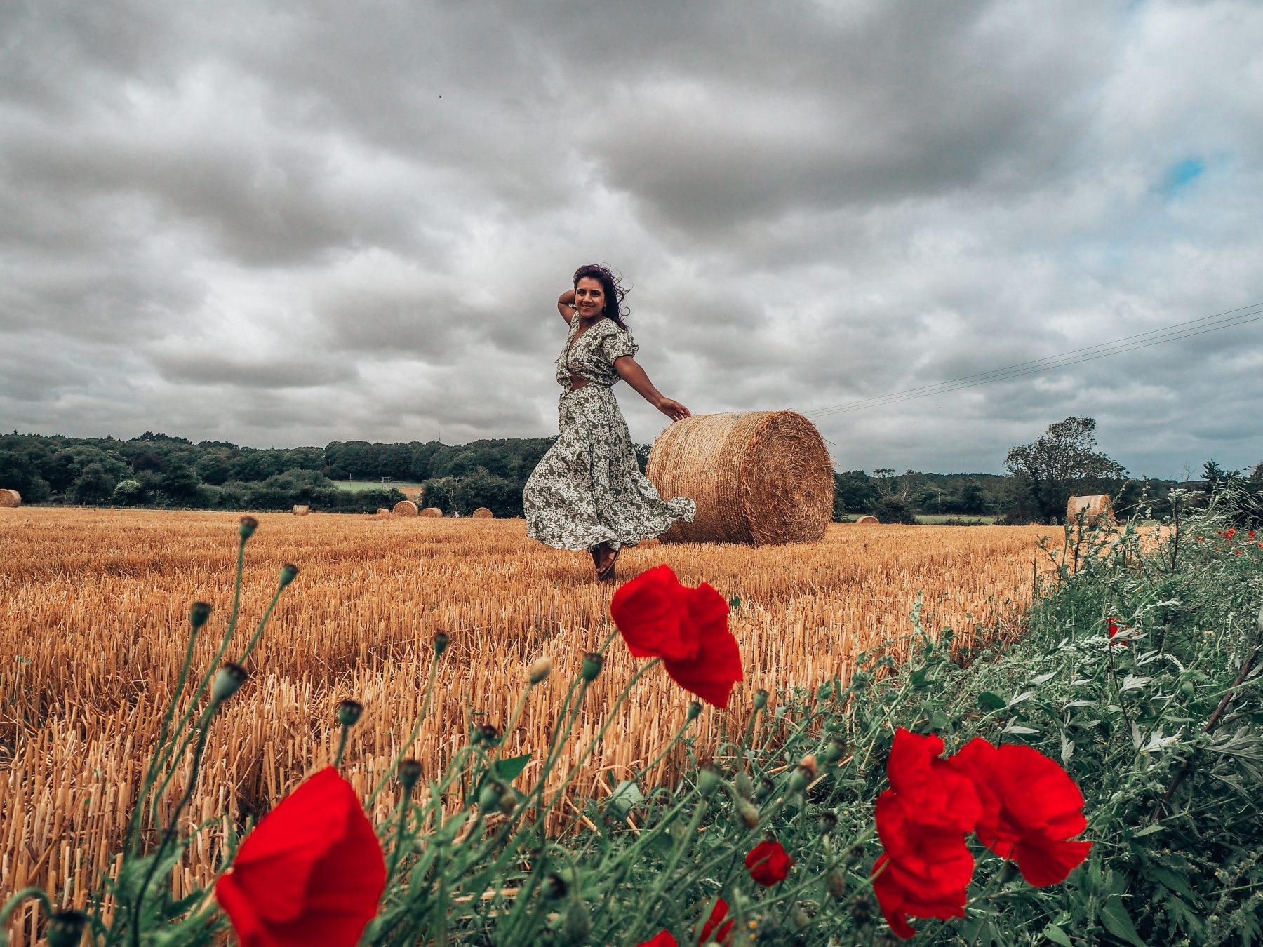 Making career plans in the countryside - dancing in front of hay bale, norfolk