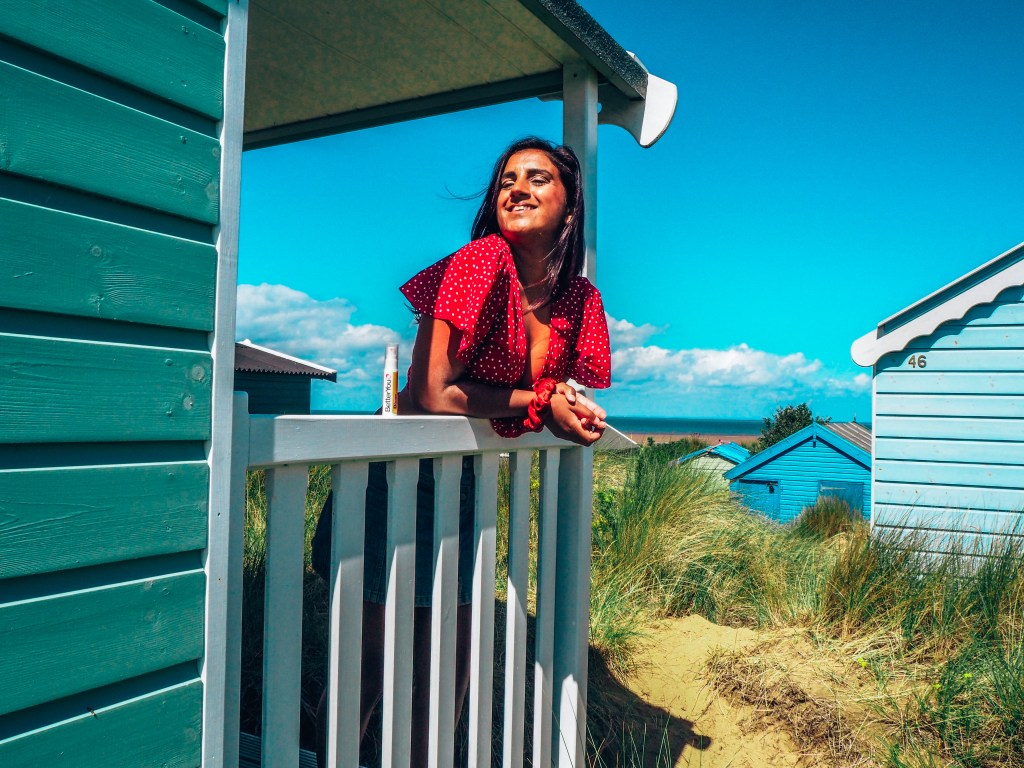 Girl in red top on beach hut with blue sky background, betteryou boost B12 supplement. boost your energy levels
