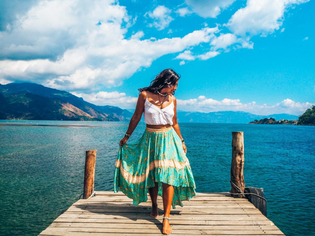 Lake Atitlan, girl in turquoise skirt on jetty in front of lake surrounded by volcanoes, Guatemala
