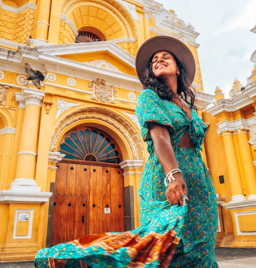 Guatemala travel itinerary, woman in green dress twirling in Antigua, Guatemala, in front of yellow church