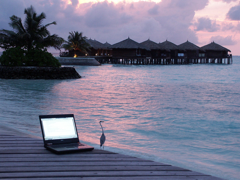 self-employed, digital nomad life, laptop with view of water huts in maldives