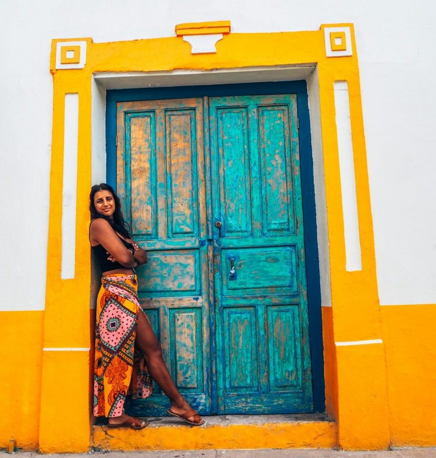 Absolutely Lucy standing in yellow skirt, black top in front of blue door with yellow and white framing in Guatemala. Sexual harassment as a solo female traveller