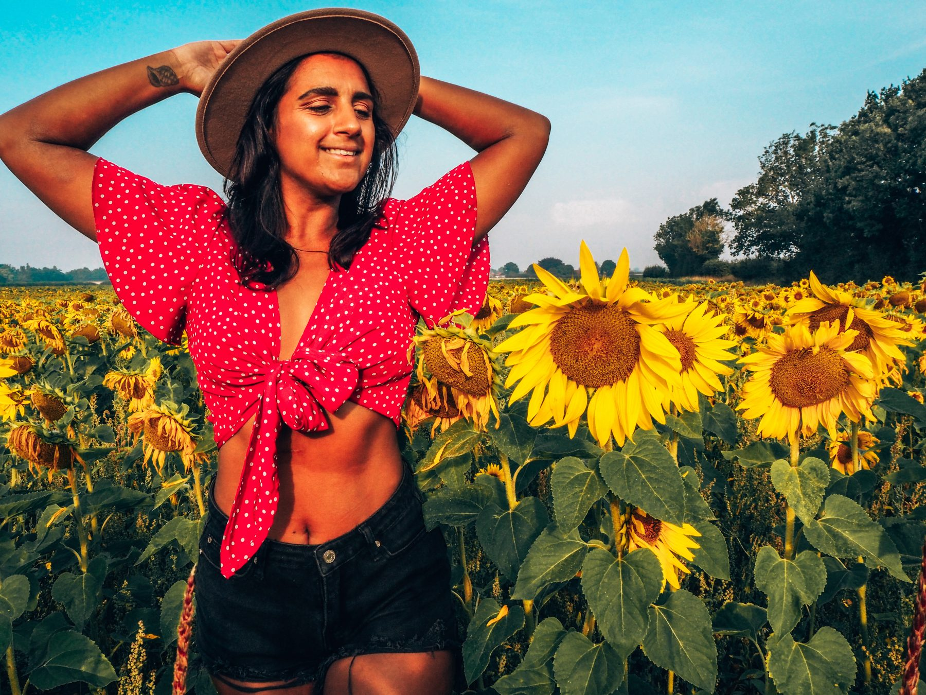 self-care rituals, absolutely lucy in red top and hat in sunflower field