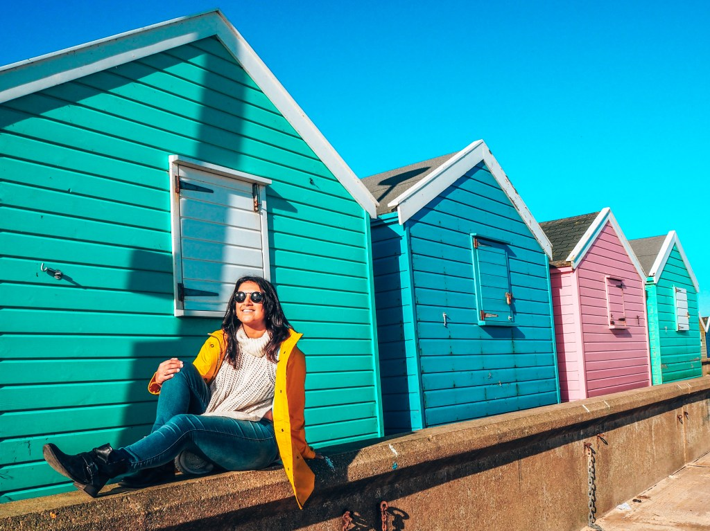 Lucy in yellow waterproof jacket in front of colourful beach huts southwold, suffolk. Things to do in southwold